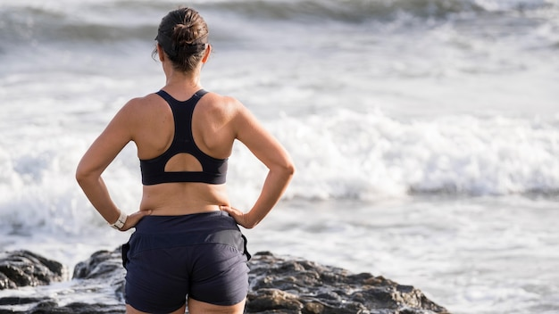 Женщина вид спереди, наслаждаясь побережьем Бесплатные Фотографии