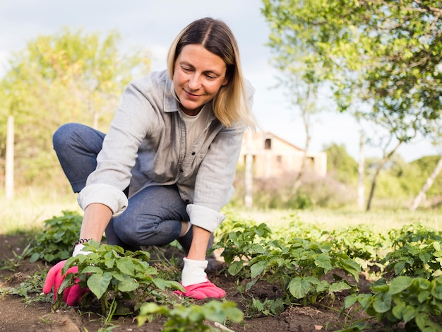 Front view woman gardening outdoors Free Photo