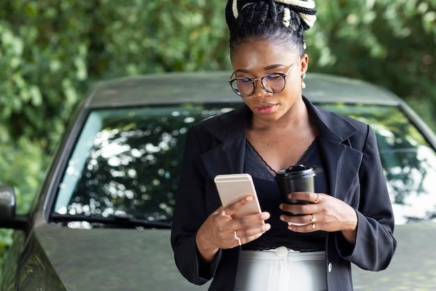 Vista frontale della donna che mangia un caffè e guarda lo smartphone mentre è appoggiato alla sua auto Foto Gratuite