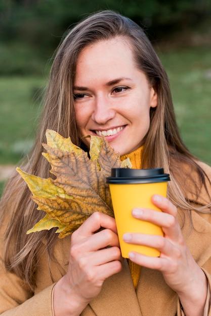 Вид спереди женщина, держащая осенние листья и чашку кофе Бесплатные Фотографии