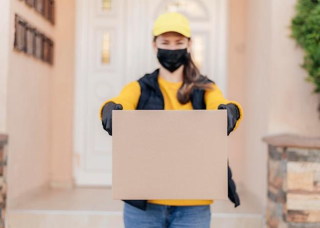 ボックスを保持している正面図の女性 無料写真