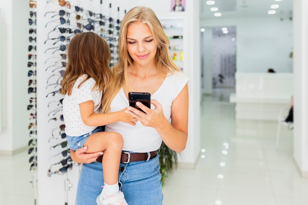 Front view of woman holding child and phone Free Photo