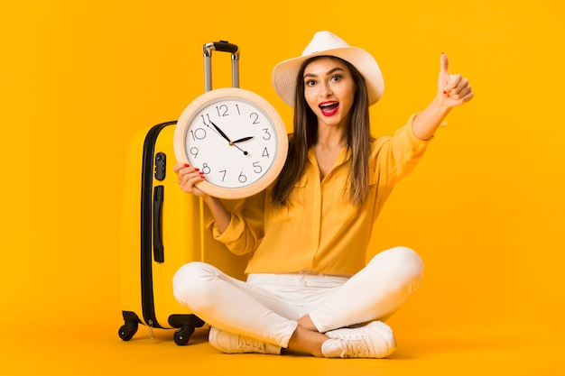 Front view of woman holding clock and giving thumbs up Free Photo