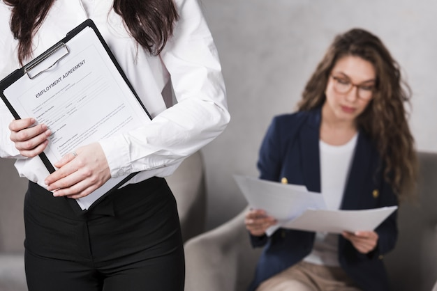 Front view of woman holding contract and another one reading papers Free Photo