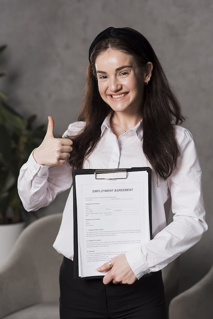Front view of woman holding contract and giving thumbs up Free Photo