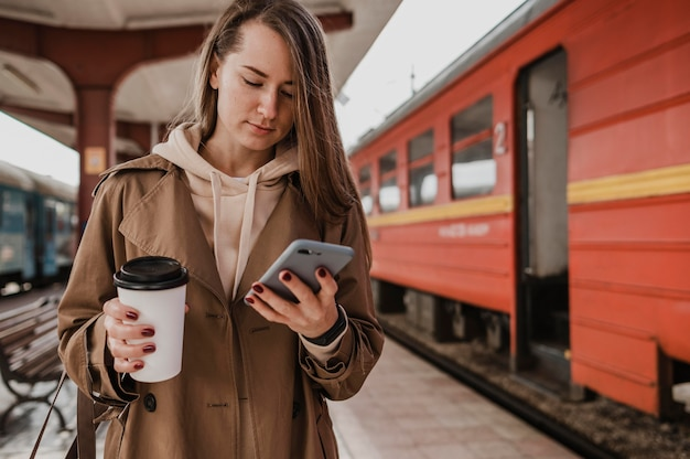 Front view woman holding a cup of coffee at the train station Free Photo