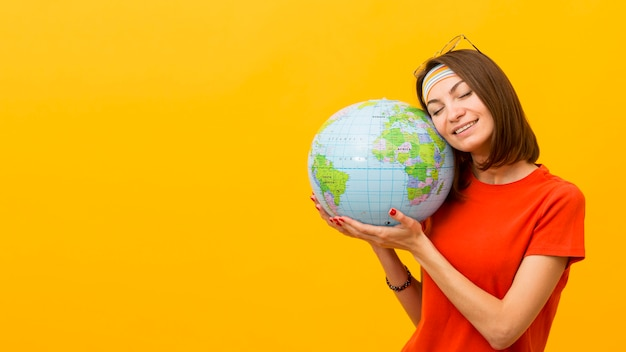 Front view of woman holding globe with copy space Free Photo