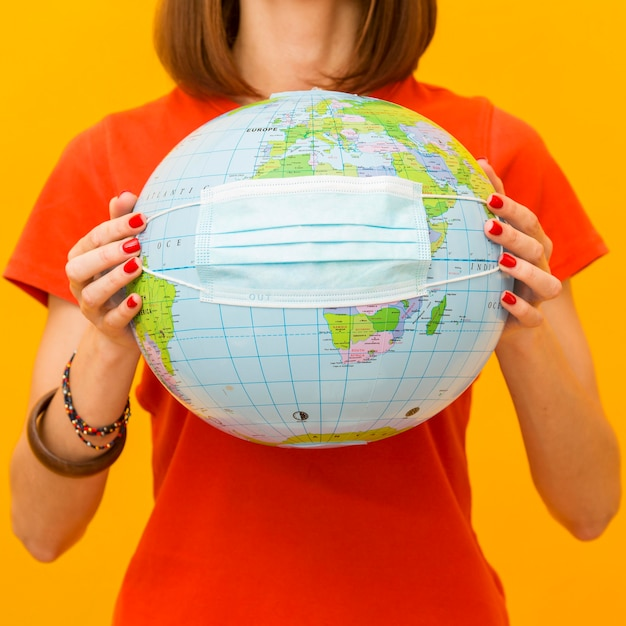 Front view of woman holding globe with medical mask Free Photo