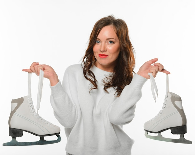 Front view woman holding ice skates Free Photo