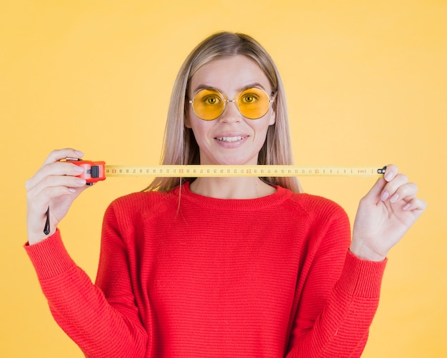 Front view woman holding measuring tape Free Photo