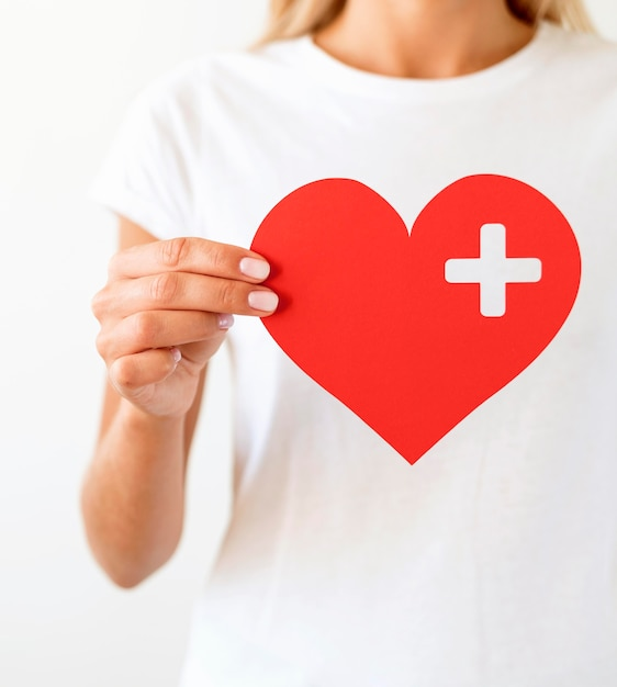 Front view of woman holding paper heart Free Photo