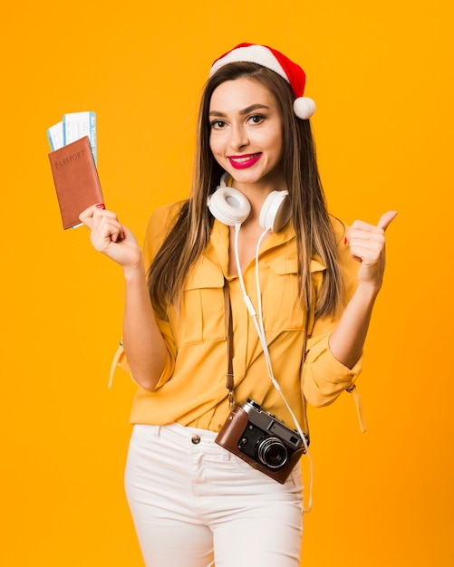 Front view of woman holding passport with plane tickets and giving thumbs up Free Photo