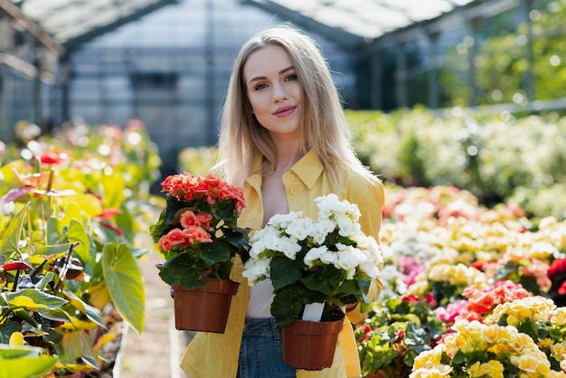 Front view woman holding pots with flowers Free Photo