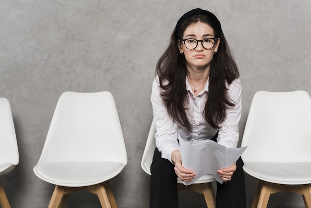 Front view of woman holding resume and waiting for her job interview Premium Photo