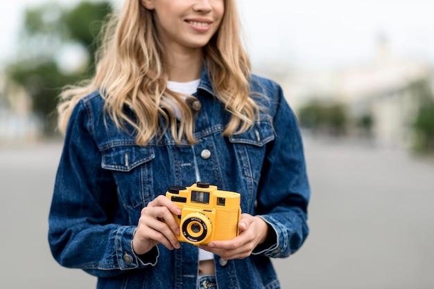 Donna di vista frontale che tiene una retro macchina fotografica gialla Foto Gratuite