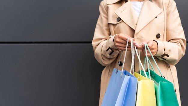 Vista frontale della donna che tiene i sacchetti della spesa con lo spazio della copia Foto Gratuite