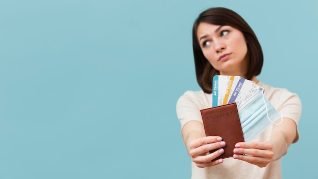 Front view woman holding some airplane tickets with copy space Free Photo