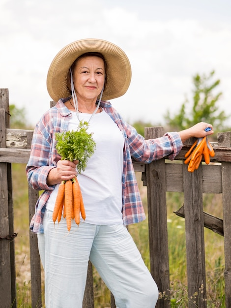 Front view woman holding some carrots in her hand Free Photo