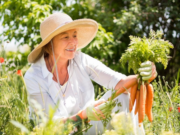 Front view woman holding some fresh carrots in her hand Free Photo