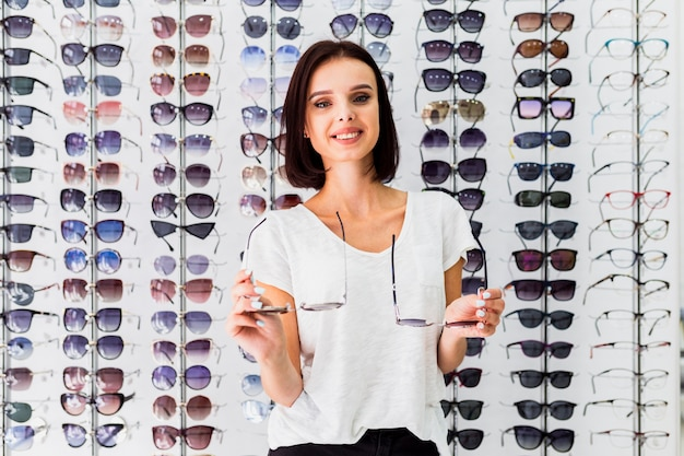 Front view of woman holding sunglasses pairs Free Photo