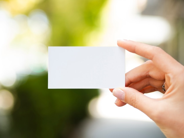 Front view woman holding up a business card mock-up Free Photo