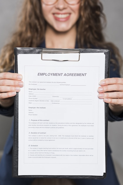 Front view of woman holding up contract for new job Free Photo