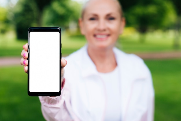 Front view woman holding up a smartphone Free Photo