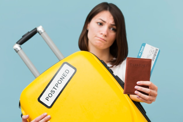 Front view woman holding a yellow baggage with a postponed sign Free Photo