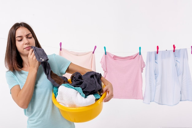 Front view woman holding a yellow laundry basket Free Photo