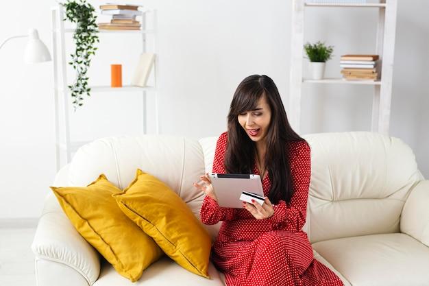 Vista frontale della donna a casa ordinare gli articoli in vendita utilizzando tablet e carta di credito Foto Gratuite