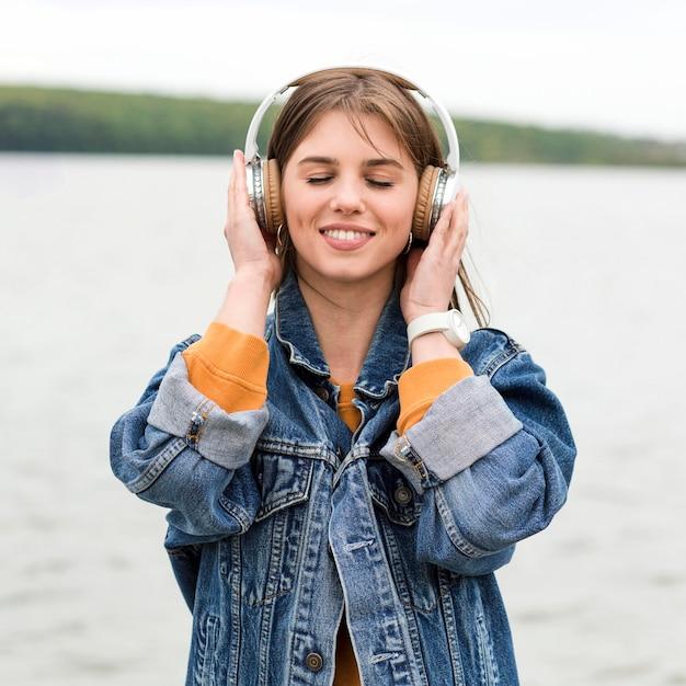 Женщина вид спереди слушает музыку на берегу моря Premium Фотографии