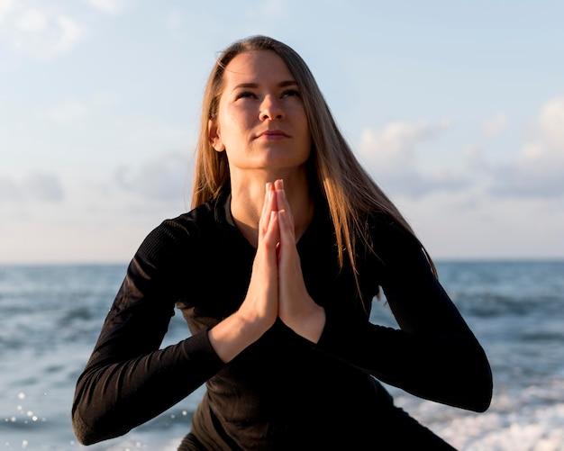 Donna di vista frontale meditando in spiaggia Foto Gratuite