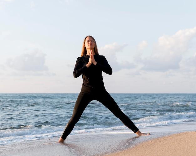 Вид спереди женщина медитирует на песке Бесплатные Фотографии
