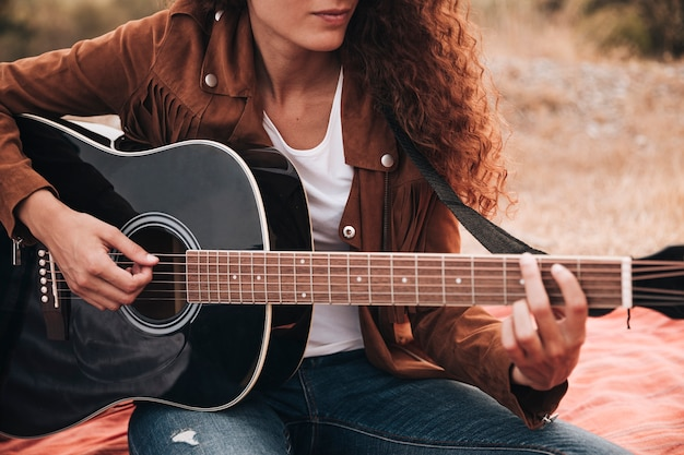 Front view woman playing guitar Free Photo