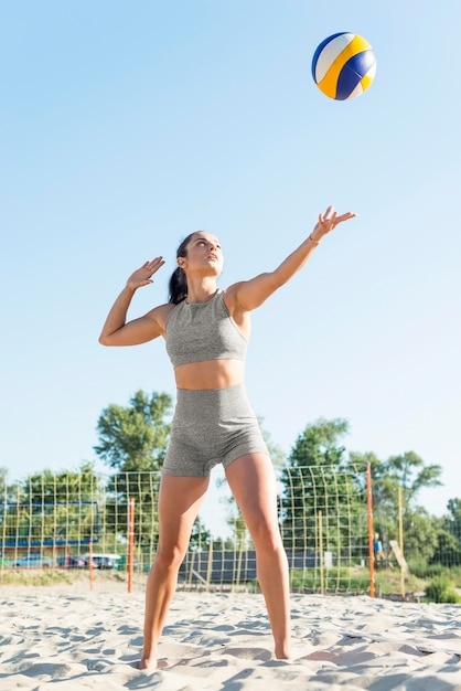 Vista frontale della donna che gioca a pallavolo sulla spiaggia Foto Gratuite