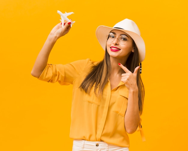 Front view of woman pointing at plane figurine that she's holding Free Photo