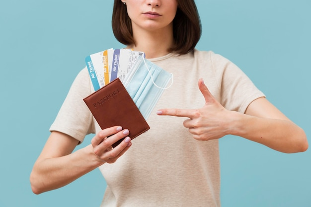 Front view woman pointing to some airplane tickets Free Photo