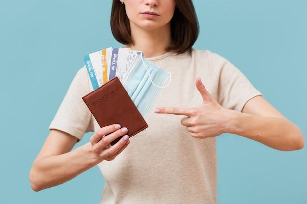 Женщина вид спереди, указывая на некоторые билеты на самолет Бесплатные Фотографии