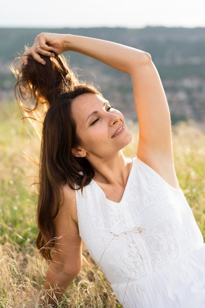 Front view of woman posing in grass outdoors Free Photo
