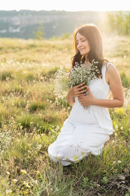 Front view of woman posing in grass with flowers Free Photo