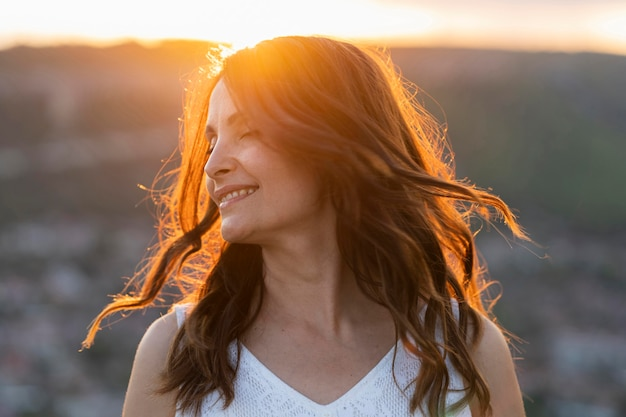 Front view of woman posing outdoors in the sunset Free Photo