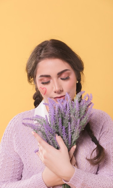 Front view of woman posing while smelling lavender Free Photo