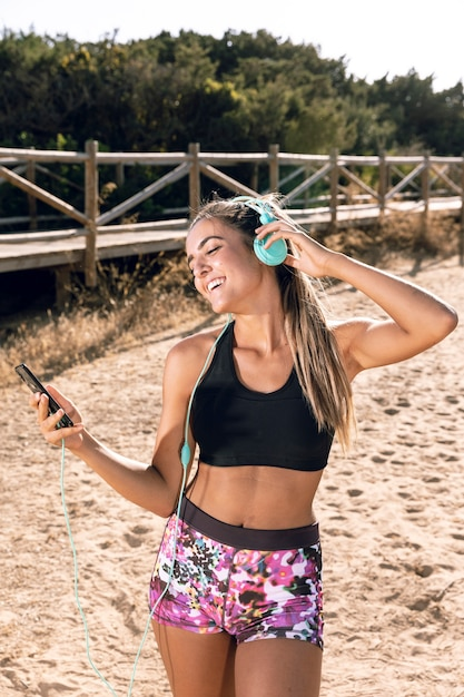Front view woman putting music on her headphones Free Photo