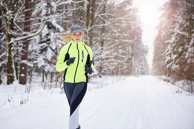 Front view of woman running in winter forest Free Photo