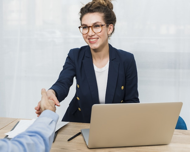 Front view of woman shaking hand with man coming for job interview Premium Photo