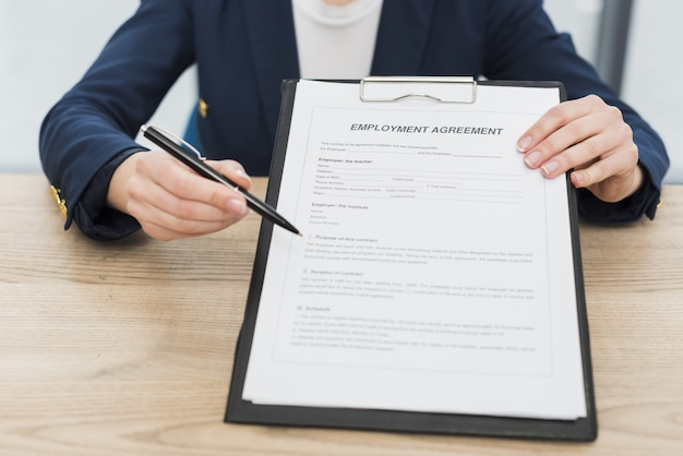 Front view of woman showing you where to sign new contract Premium Photo