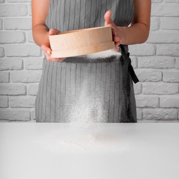 Vista frontale donna che setaccia farina Foto Gratuite