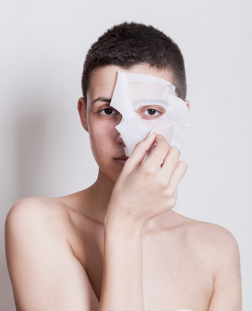 Front view woman taking off her face mask Free Photo