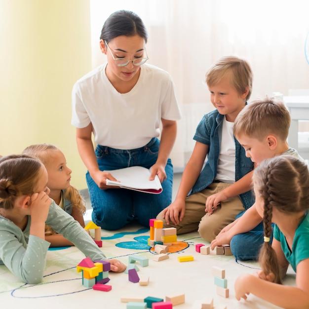 幼稚園で子供たちを教える正面女性 Premium写真