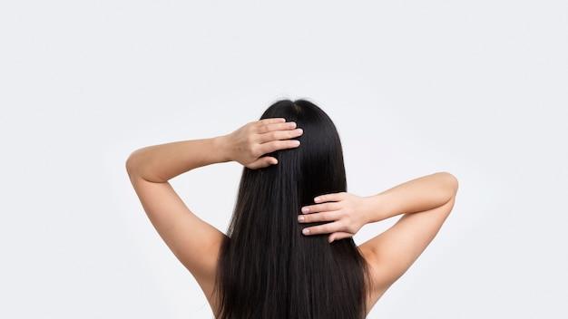 Женщина вид спереди касаясь ее волосы Premium Фотографии